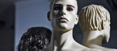 White skinned male mannequin, lighted from the right side of the image, sitting behind a large shop window. It has strong features, colorful eyes and plastic hair. Behind it there are two other models, another white one and a female mannequin with shiny black hair.