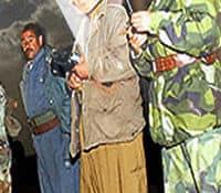 Members of the Kurdish militia listen to a radio as President Bush's deadline expires.