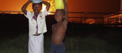 Kids in front of gas flare in Niger Delta, 2007 (© Elaine Gilligan)