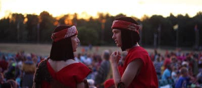 Two costumed Israelites talk as the crowd gathers for the Hill Cumorah Pageant.