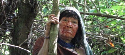 Noemi Vagus, an Ashaninka shaman, standing in front of an Ayahuasca vine in the Peruvian Amazon