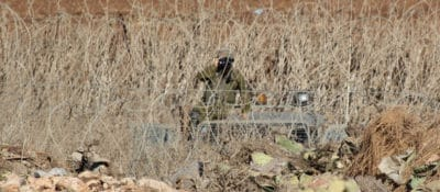 At the edge of the West Bank village of Faqqua, an Israeli soldier watches from the other side of the Green Line. Photo by Bryan MacCormack of Left in Focus.